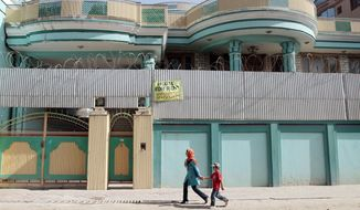 Afghans walk past by a house for rent in Kabul, Afghanistan. A real estate broker, Mir Ahmad Shah, said the market is the worst in his seven years of selling properties in the capital. No one wants to buy due to instability and the 2014 departure of NATO forces. (Associated Press)