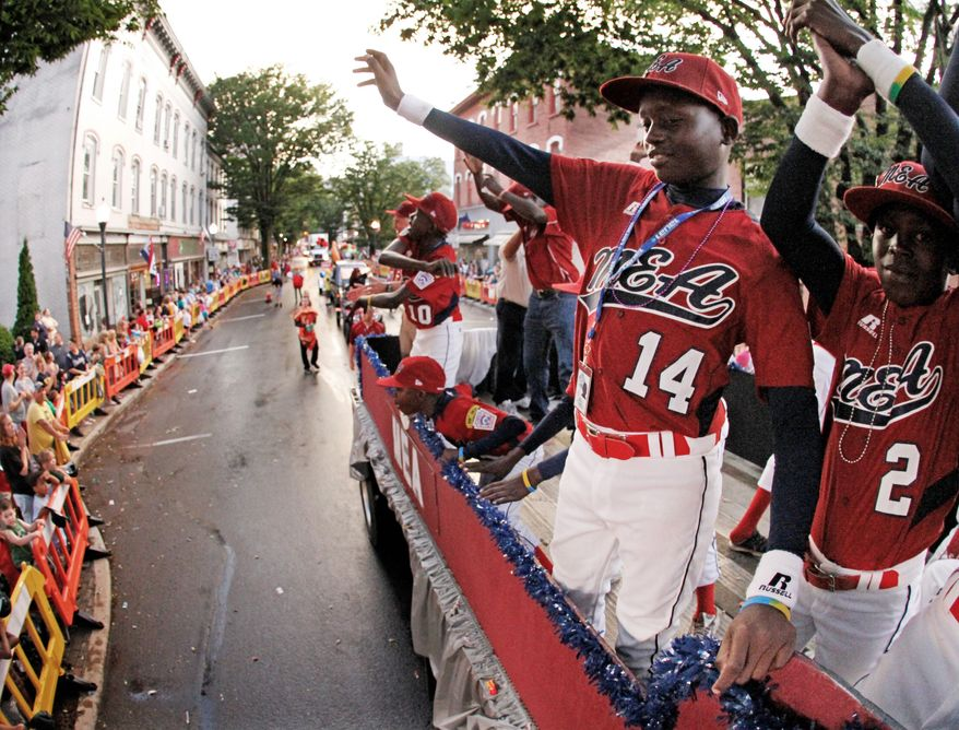 Team members from Lugazi, Uganda, make their way through downtown Williamsport, Pa., during a ride in the Little League Grand Slam Parade on Wednesday. (Associated Press)