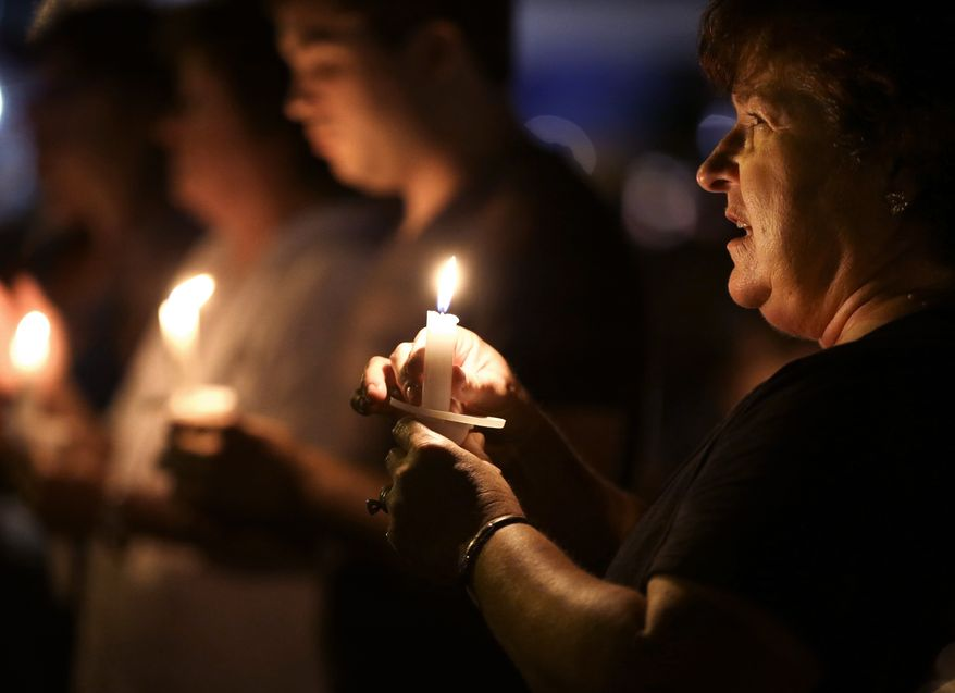 Denise Recatto (right) of Baton Rouge, La., sings with other Elvis Presley fans during the annual candlelight vigil at Graceland, Presley's home in Memphis, Tenn., on Wednesday, Aug. 15, 2012. (AP Photo/Mark Humphrey)