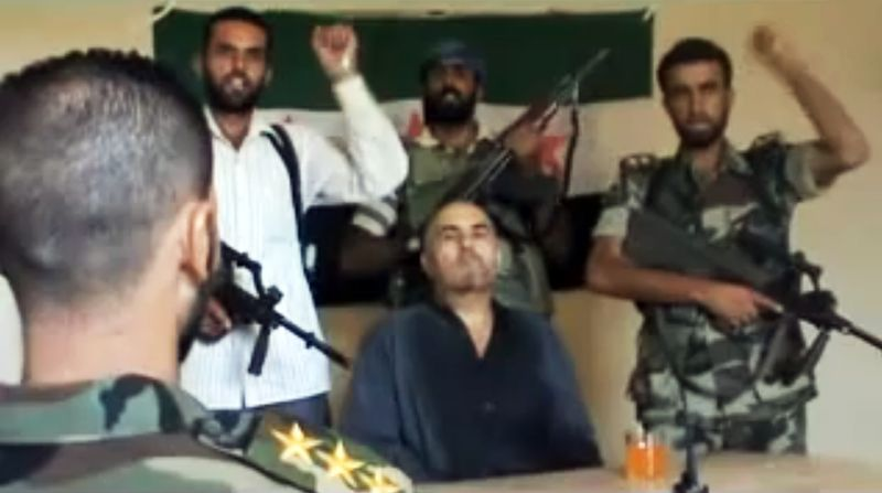 This image made from amateur video released by the Shaam News Network purports to show Syrian Pilot Col. Rafik Mohammed Suleiman being interrogated by a rebel officer Aug. 13, 2012, after his Soviet-made MiG warplane was apparently hit by ground fire