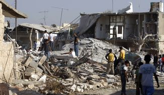 Syrians check the damage to houses Aug. 15, 2012, after an air strike destroyed at least ten houses in the town of Azaz on the outskirts of Aleppo, Syria. (Associated Press)