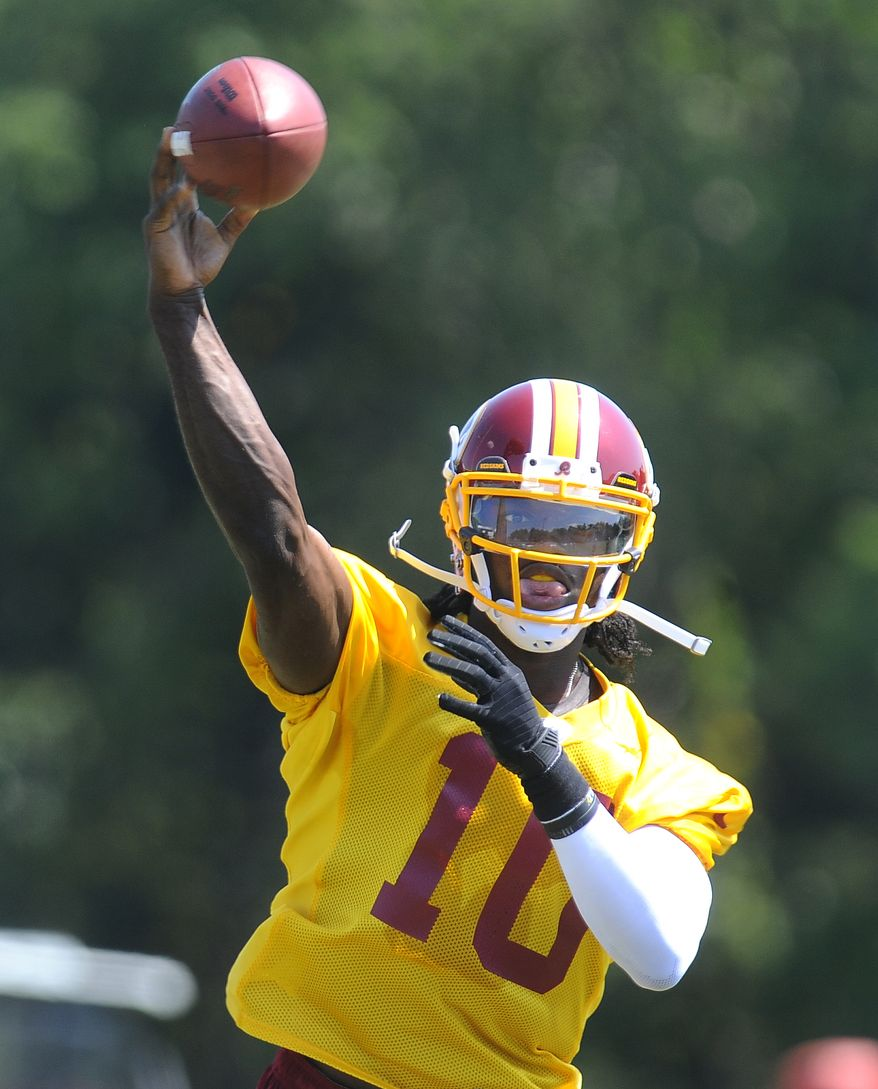 Washington Redskins rookie quarterback Robert Griffin III throws a pass during team practice at their Redskins training camp, Thursday, Aug. 16, 2012, in Ashburn, Va. (AP Photo/Richard Lipski)