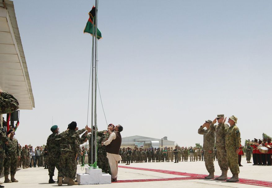 **FILE** Afghan security forces raise Afghanistan's flag in place of NATO's flag on July 18, 2012, during the third phase of transfer of authority from NATO troops to Afghan security forces in Kandahar, Afghanistan. (Associated Press)
