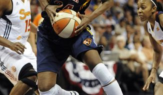 Indiana Fever's Tamika Catchings, center, drives past Connecticut Sun's Asjha Jones, left, and Renee Montgomery during the second half of a WNBA basketball game in Uncasville, Conn., Tuesday, June 19, 2012. Connecticut won in overtime, 88-85. (AP Photo/Jessica Hill)