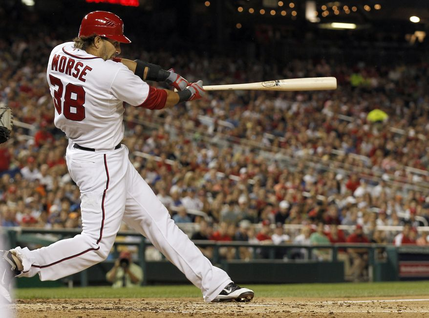 Washington Nationals' Michael Morse follows through on a grand slam during the fourth inning of a baseball game against the New York Mets at Nationals Park on Friday, Aug. 17, 2012, in Washington. The Nationals won 6-4. (AP Photo/Alex Brandon)