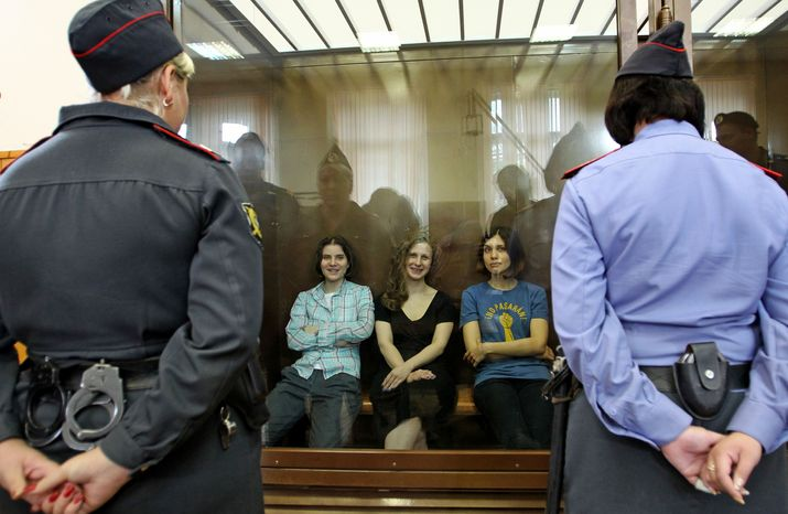 """**FILE** Feminist punk group Pussy Riot members (from left) Yekaterina Samutsevich, Maria Alekhina and Nadezhda Tolokonnikova sit Aug. 17, 2012, in a glass cage at a courtroom in Moscow. The women, two of whom have young children, are charged with hooliganism connected to religious hatred but the case is widely seen as a warning that authorities will only tolerate opposition under tightly controlled conditions. The t-shirt worn by Tolokonnikova says, in Spanish, """"They shall not pass,"""" a slogan often used to express determination to defend a position against an enemy. (Associated Press)"""