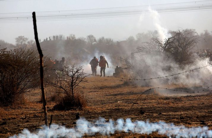 Striking mineworkers are caught Aug. 16, 2012, in tear gas as police open fire on striking miners at the Lonmin Platinum Mine near Rustenburg, South Africa. (Associated Press)