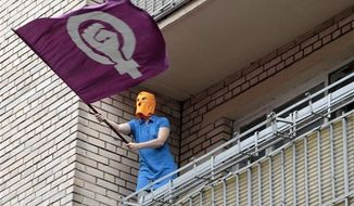 A masked supporter of the Russian punk group Pussy Riot waves a feminist flag from a balcony of a building at the court in Moscow, Russia, Friday, Aug. 17, 2012. A Moscow judge has sentenced each of three members of the provocative punk band Pussy Riot to two years in prison on hooliganism charges following a trial that has drawn international outrage as an emblem of Russia's intolerance to dissent. (AP Photo/Misha Japaridze)