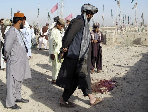 Afghans look at a pool of blood at the scene of an explosion Aug. 19, 2012, at a cemetery in Lashkar Gah, Afghanistan. A bomb hidden in the cemetery exploded as a police official and his family were visiting the grave of a relative, killing the official and his brother, police said. (Associated Press)