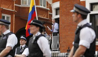 Surrounded by British police, WikiLeaks founder Julian Assange (center) makes a statement to the media and supporters from a window of Ecuadorean Embassy in central London on Sunday, Aug. 19, 2012. (AP Photo/Sang Tan)