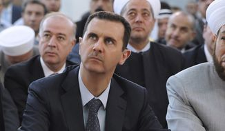 Syrian President Bashar Assad performs Eid prayers at the Hamad mosque in Damascus, Syria, on Sunday, Aug. 19, 2012, to mark Eid al-Fitr, a three-day holiday ending the holy month of Ramadan. (AP Photo/SANA)
