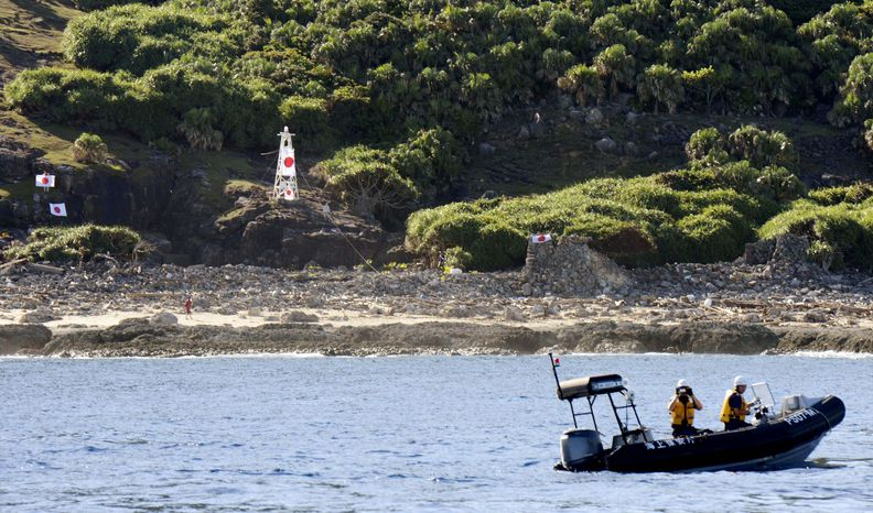 Japanese coast guard officers patrol in a rubber boat as Japanese activists hang their national flag on a small lighthouse and its perimeter on Uotsuri, the largest island in a small archipelago known in Japan as the Senkaku Islands and in China as the Diaoyu Islands, on Sunday, Aug. 19, 2012. (AP Photo/Kyodo News)