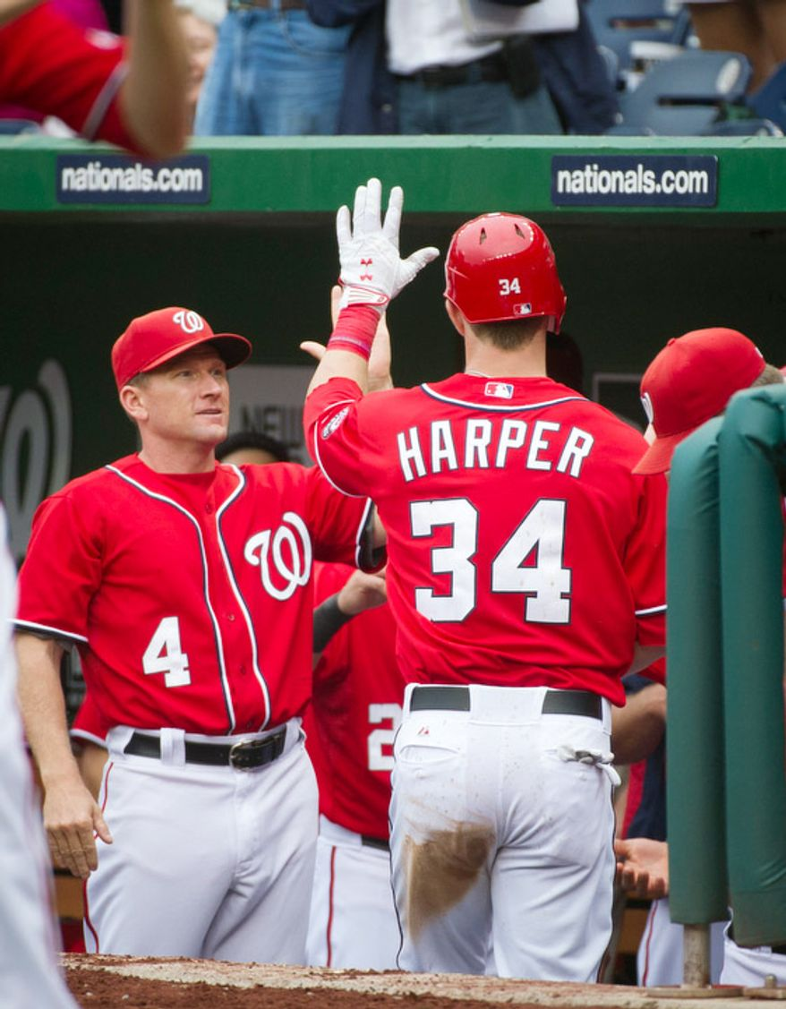 Washington Nationals Bryce Harper is greeted at the dugout by Rick Eckstein (4) after his solo home run in the bottom of the fifth inning. The Nationals defeated the Mets 5-2. (Rod Lamkey Jr./The Washington Times)