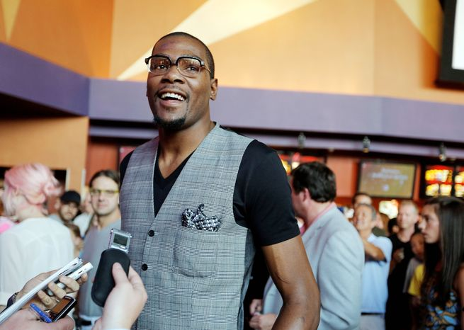 """Basketball star Kevin Durant walks the red carpet Sunday during the premiere of his new movie, """"Thunderstruck,"""" in Oklahoma City. The three-time NBA scoring champion and Olympic gold medalist plays himself in the film, about a fan who magically absorbs Durant's skill set. (The Oklahoman via Associated Press)"""