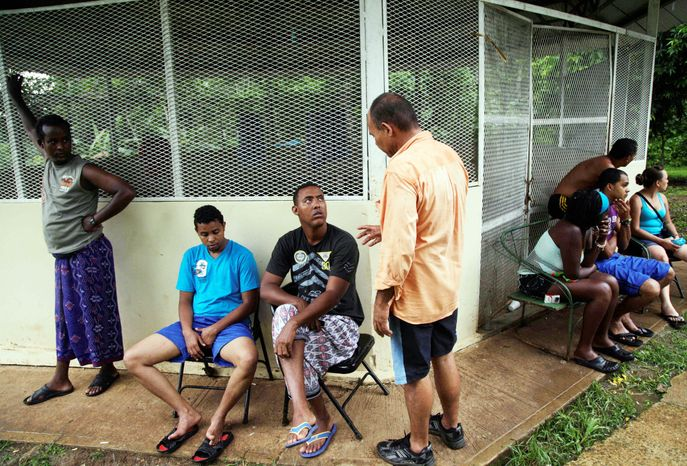 Cuban migrant Mayra Reyes, fourth from right, rests at a shelter with other Cubans with whom she traveled, along with migrants from Bangladesh, after being caught by Panamanian bo