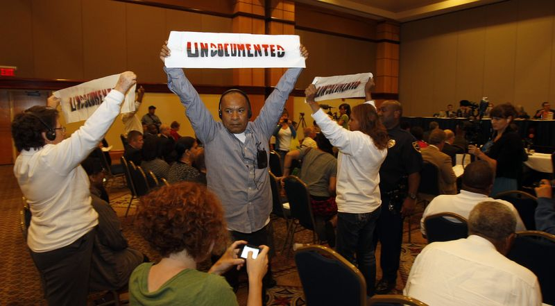 Police escort protesters from the room Aug. 17, 2012, after disrupting Kris Kobach, Secretary of State from Kansas, as he addressed the Commission at the U.S. Commission on Civil Rights Immigration Briefing in Birmingham, Ala. (Associated Press/Southern Poverty Law Center, Butch Dill)