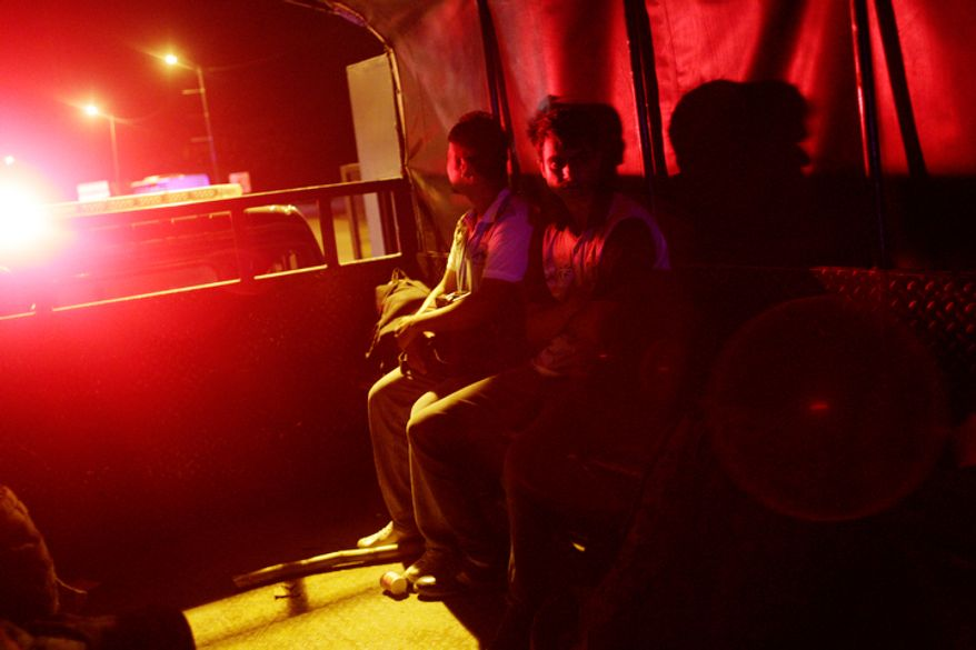 Two migrants from Bangladesh sit inside a police car after being found in the Darien province by Panama border police in Panama City.  (AP Photo/Arnulfo Franco)