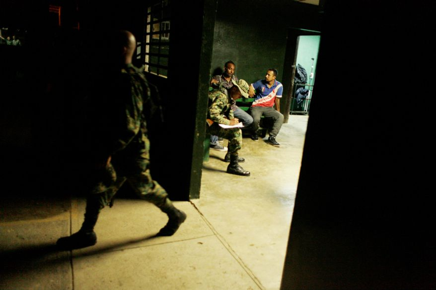 A Panama border police officer questions two migrants from India at a police station in the Darien province on the border with Colombia, in Yaviza, Panama.  (AP Photo/Arnulfo Franco)