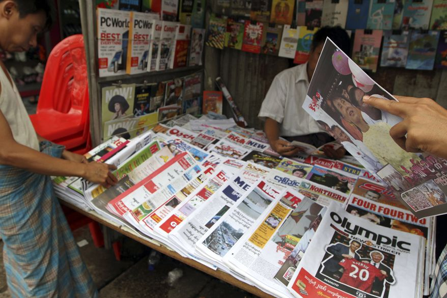 Customers buy local weekly journals at a roadside shop in Yangon, Myanmar, on Monday, Aug. 20, 2012. (AP Photo/Khin Maung Win)
