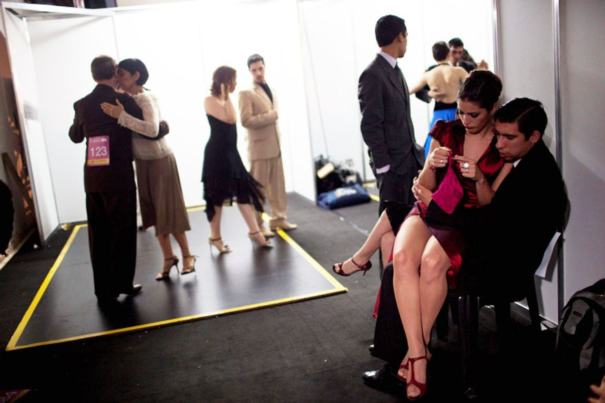 Participants wait backstage before competing during the 2012 Tango Dance World Cup in Buenos Aires, Argentina, Monday, Aug. 20, 2012. The two-week long event offers more than 500 free dance lessons, concerts and recitals. Hundreds of professional dancers compete in the championship and teach many the eight basic steps of the dance in the city where it was born. (AP Photo/Natacha Pisarenko)