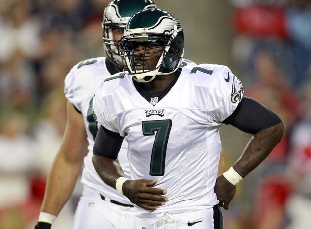 **RETRANSMITTED WITH ALTERNATE CROP FBO110**Philadelphia Eagles quarterback Michael Vick (7) holds his mid-section after getting hit hard by New England Patriots linebacker Jermaine Cunningham (96) during the first quarter of an NFL preseason football game in Foxborough, Mass., Monday, Aug. 20, 2012.  Vick left the game after the play. (AP Photo/Steven Senne)