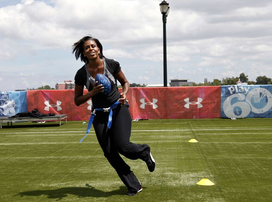 """** FILE ** First lady Michelle Obama turns and runs after catching a pass while participating in her """"Let's Move!"""" campaign and the NFL's Play 60 campaign festivities with area youth in New Orleans on Sept. 8, 2010. (AP Photo/Gerald Herbert)"""