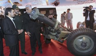 Iranian President Mahmoud Ahmadinejad (left) listens to an official as he looks at a mortar launcher, while his defense minister, Gen. Ahmad Vahidi (second from left), looks on during a ceremony to unveil Iranian-made weapons and to mark the national day of Iran's defense industry on Tuesday, Aug. 21, 2012. (AP Photo/Iranian Presidency Office, Mohsen Rafinejad)
