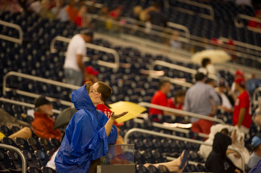 Beth Coleman, of Fredericksburg, Va., holds out her hand for rain Aug. 20, 2012, during a rain delay as the Washington Nationals host the Atlanta Braves at Nationals Park in Washington, D.C. (Rod Lamkey Jr./The Washington Times)