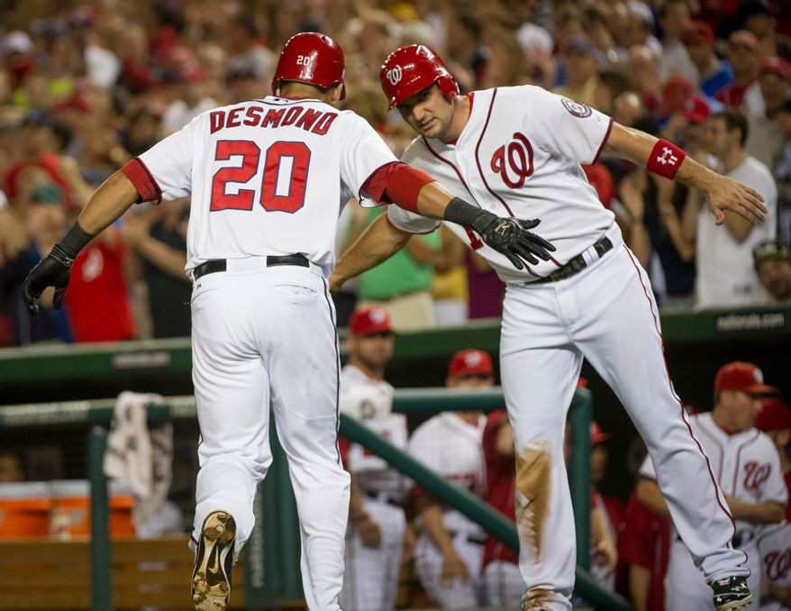 Washington Nationals SS Ian Desmond (20) is greeted at home plate by Ryan Zimmerman after hitting a 3-run home run in the first inning of the Nationals' 5-4, 13-inning home victory over the Atlanta Braves on Aug. 20, 2012. (Rod Lamkey Jr./The Washington Times)