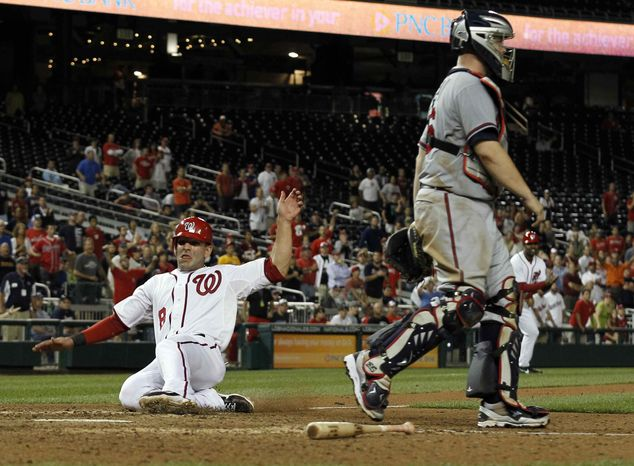 Washington Nationals' Danny Espinosa scores the winning run after Chad Tracy reached to first on an error with Atlanta Braves catcher Brian McCann at right, during the 13th inning of a baseball game at Nationals Park on Tuesday, Aug. 21, 2012, in Washington. The Nationals won 5-4 in 13 innings. (AP Photo/Alex Brandon)
