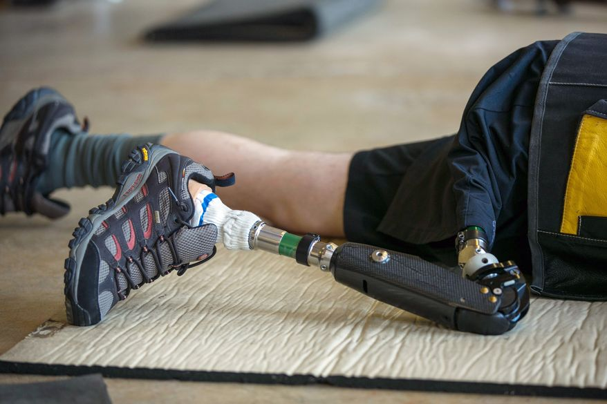 SFC Josh Olson, a U.S. Army Paralympic marksman, prosthetic leg supports him in preparation to shoot his rifle at Wagner Range, in Ft. Benning, Ga., Thursday, May 31, 2012. Olson sustained heavy damage to his leg during an ambush attack in Iraq in 2003, in which his right leg had to be amputated. He's currently a apart of the wounded warrior program and the first active duty soldier to qualify for a Paralympics in the field of mixed 50 meter rifle and mixed 10 meter air rifle. (Andrew S. Geraci/The Washington Times)
