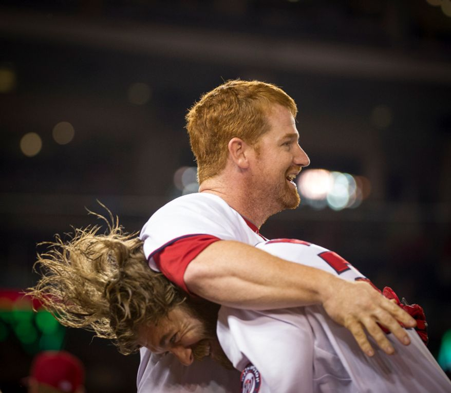 Washington Nationals Chad Tracy is lifted up and hugged by Jayson Werth (below) after his RBI single defeated the Atlanta Braves 5-4 at Nationals Park in Washington, D.C., Tuesday, Aug. 21, 2012. (Rod Lamkey Jr./The Washington Times)