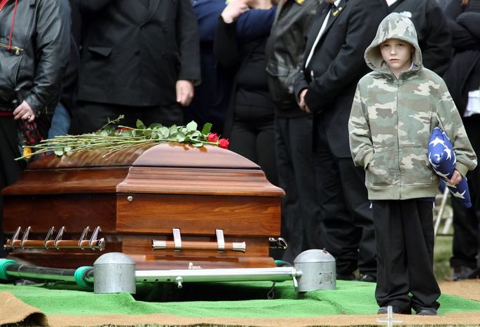 Nicholas Weichel stands next to the casket of his father, Rhode Island National Guard Sgt. Dennis Weichel Jr., who was killed in Afghanistan. The conflict is no longer a hot topic with most Americans, even with 88,000 U.S. troops still fighting there and 2,000 having died there. (Associated Press)