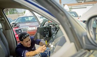 Eddy Torres of VeriFone installs the new Taxi Smart Meter System in a cab. It will enable passengers to pay with credit cards and also to watch news, weather reports and current events on TV minimonitors mounted on the seats. (Rod Lamkey Jr./The Washington Times)