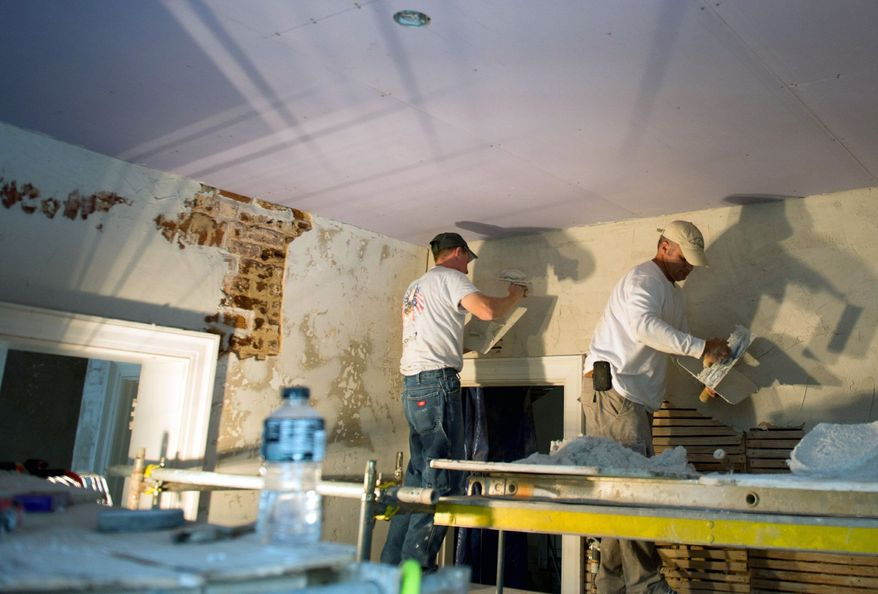Restoration masons Justin Rivenburgh (left) and Tim Winther work in Mineral, Va., to repair the historic Cuckoo house, which was damaged by the 5.8-magnitude earthquake that shook the region last August. (Andrew Harnik/The Washington Times)