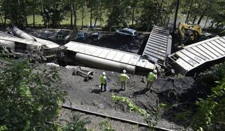 On Tuesday, Aug. 21, 2012, officials inspect part of a CSX freight train that derailed alongside a parking lot the night before in Ellicott City, Md. (AP Photo/Patrick Semansky)