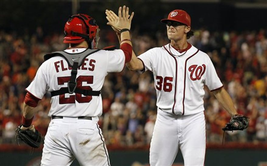 Washington Nationals catcher Jesus Flores celebrates with closer Tyler Clippard after the Washington Nationals closed out a 4-1 win over the Atlanta Braves on Tuesday, Aug. 21, 2012, in Washington. (AP Photo/Alex Brandon)