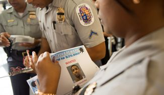 Prince George's County police officers hand out wanted fliers to members of the media for Kevon Darnell Neal, 23, of Fort Washington, wanted in connection to an auto theft which led to Police Officer Adrian Morris' death Monday night, Palmer Park, Md., Wednesday, August 22, 2012. Police have already arrested Kenneth Clark Mitchell, 25, of the District in connection with the incident. (Andrew Harnik/The Washington Times)