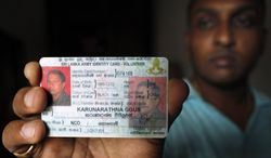 In this photo taken May 7, 2012, Ravindra Udayashantha, a 38-year-old town council chairman, displays an army identity card that he seized from one of the men from a white van, in Kolonnawa, suburb of Colombo, Sri Lanka. Udayashantha dramatically pre-empted an abduction attempt when he and his entourage surrounded the men from a suspicious white van that pulled alongside him at a Colombo park and captured them. Eventually, at gunpoint, the men admitted who they were: Sri Lankan government soldiers. In Sri Lanka, anyone who has crossed someone of importance is wary of white vans, said to be the vehicles of choice for shadowy squads who ''disappear'' opponents of powerful people. (AP Photo/Gemunu Amarasinghe)