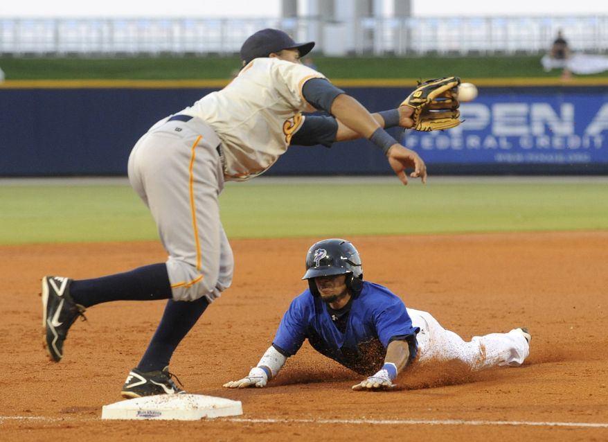 Pensacola Blue Wahoos' Billy Hamilton slides under Montgomery third baseman Omar Luna for a stolen base, his 146th of the season, during a Double-A baseball game Tuesday, Aug. 21, 2012, in Pensacola, Fla. Hamilton broke the record for steals by minor league teams affiliated with big league organizations set by Vince Coleman in 1983 with 145 for Macon in the Class A South Atlantic League. (AP Photo/Pensacola News Journal, Ben Twingley) NO SALES