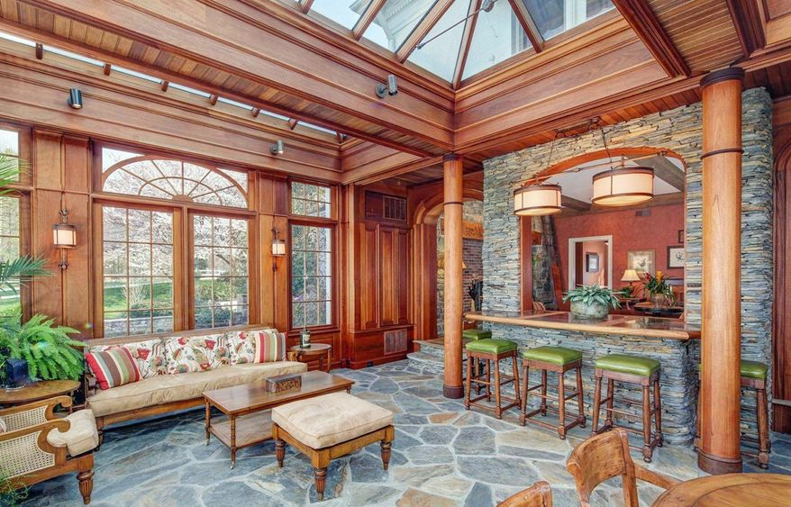 The sunroom has a slate floor, cathedral ceiling with glass and wood beams and a full-size stone wet bar. The sunroom has doors to the patio.