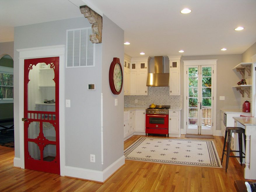 The kitchen features white cabinets with splashes of red.