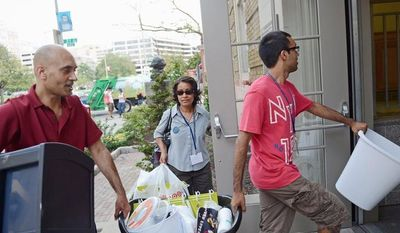 Noah Yosif, 17, gets help moving to his dorm room from his parents, Benjamin Yosif and Reshma Ahmed, a day before the official move-in day for students at George Washington University in Washington, D.C., on Thursday. At top area colleges, applications for admission are actually up, despite economic stagnation at the national level. (Rod Lamkey Jr./The Washington Times)