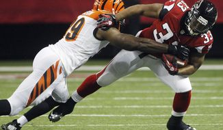 Cincinnati Bengals linebacker Manny Lawson (99) defends against Atlanta Falcons running back Michael Turner (33) during the first half of an NFL preseason football game, Thursday, Aug. 16, 2012, in Atlanta. (AP Photo/John Bazemore)