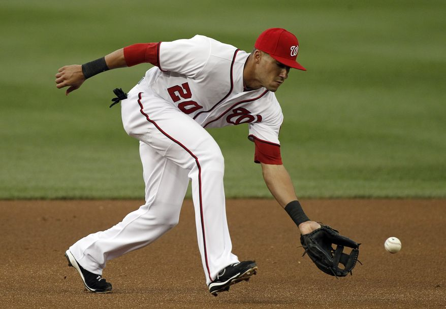 Washington Nationals shortstop Ian Desmond fields a ball to make the out on Atlanta Braves' Martin Prado during the first inning of a baseball game at Nationals Park on Tuesday, Aug. 21, 2012, in Washington. (AP Photo/Alex Brandon)