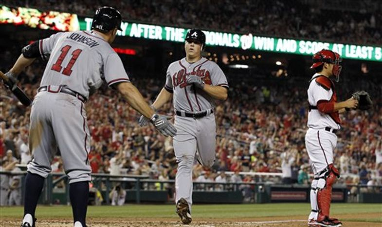 Atlanta Braves' Reed Johnson, left, celebrates with Kris Medlen (54) as Medlen scores next to Washington Nationals catcher Kurt Suzuki, right, during the fifth inning of a baseball game at Nationals Park on Wednesday, Aug. 22, 2012, in Washington. The Braves won 5-1. (AP Photo/Alex Brandon)
