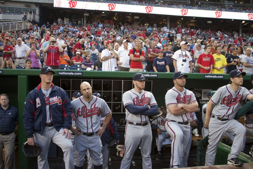 The Atlanta Braves look on from the dugout as the Washington Nationals hold ceremony before the first pitch to honor veteran third baseman Chipper Jones, Wednesday, Aug. 22, 2012, in Washington, DC. Jones has played his entire 19 year career was an Atlanta Brave, winning one World Series title with them in 1995. (Craig Bisacre/The Washington Times)