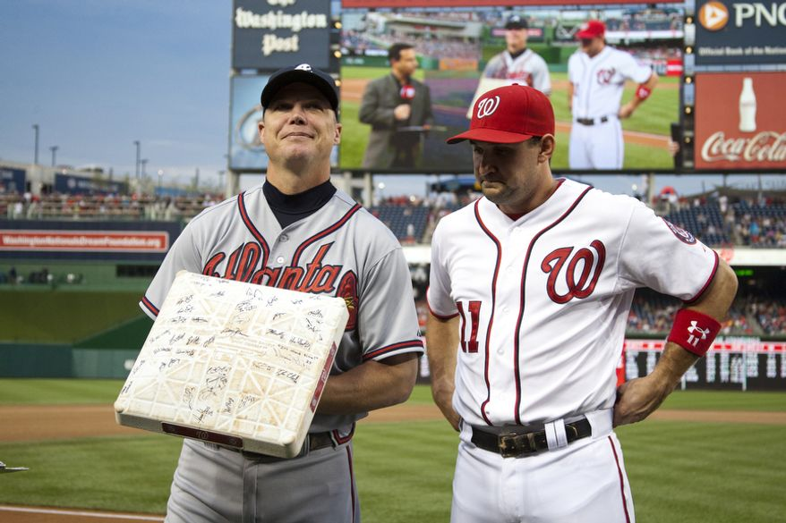 Washington Nationals, Ryan Zimmerman, presents a teamed signed third base to veteran third baseman Chipper Jones, Wednesday, Aug. 22, 2012, in Washington, DC. Jones said he would be retiring after this session. He has played his entire 19 year career was an Atlanta Brave, winning one World Series title with them in 1995.  (Craig Bisacre/The Washington Times)