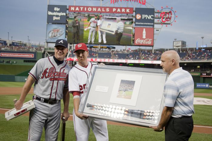 Washington Nationals, Adam LaRoche, presents the bat that Chipper Jones hit the first home run with in Nationals Ball Park, with General Manager Mike Rizzo Wednesday, Aug. 22, 2012, in Washington, DC. Jones said he would be retiring after this session. He has played his entire 19 year career was an Atlanta Brave, winning one World Series title with them in 1995.  (Craig Bisacre/The Washington Times)