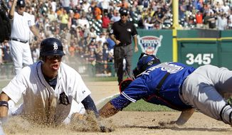 Detroit Tigers' Quentin Berry, left, scores the winning run on a Alex Avila single as Toronto Blue Jays' catcher Yorvit Torrealba, right, reaches to make a tag in the 11th inning of a baseball game on Thursday, Aug. 23, 2012, in Detroit. (AP Photo/Paul Sancya)